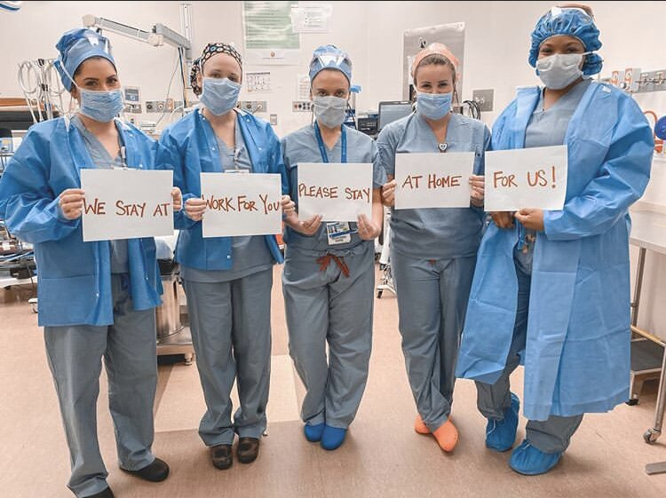 Healthcare Workers hold signs; We stay at work for you, please stay at home for us!
